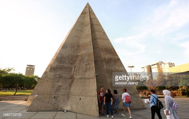 Visitors gather by the stone pyramid during an exhibiton at the grounds of the Tripoli International Fair close to the seafront of the northern...