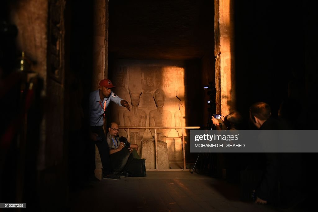 Visitors gather inside the temple of Abu Simbel, south of Aswan in upper Egypt, to witness the sun illuminate the statue of Ramses II on October 22, 2016. / AFP / MOHAMED