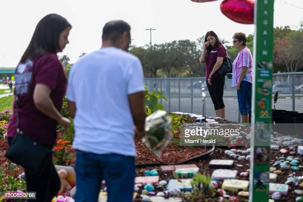 Visitors gather near a makeshift memorial outside of Marjory Stoneman Douglas High School in Parkland, Fla., on Friday, Feb. 14 during the two-year...