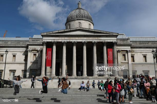 Visitors gather on the steps of the National Gallery art museum in central London on August 24, 2018.