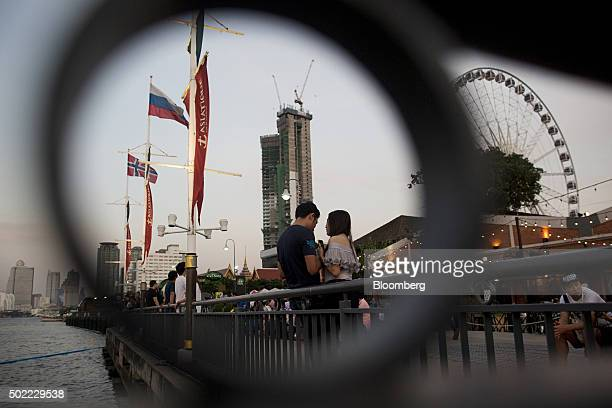 Visitors gather on the waterfront as a ferris wheel stands in the background at Asiatique The Riverfront openair mall in Bangkok Thailand on Friday...