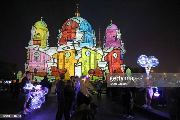Visitors gather to look at the Dom Cathedral that is bathed in an artistic light mural during the Festival of Lights on September 08, 2021 in Berlin,...