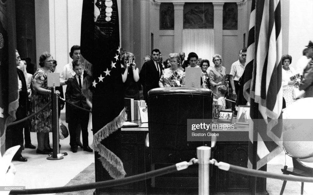 Visitors gather to view the desk used by the late President Kennedy at the traveling John F. Kennedy Library Exhibit at the Museum of Fine Arts in Boston on Aug. 19, 1964.
