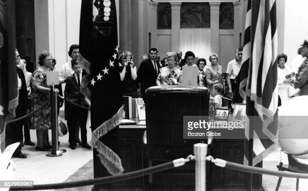 Visitors gather to view the desk used by the late President Kennedy at the traveling John F Kennedy Library Exhibit at the Museum of Fine Arts in...
