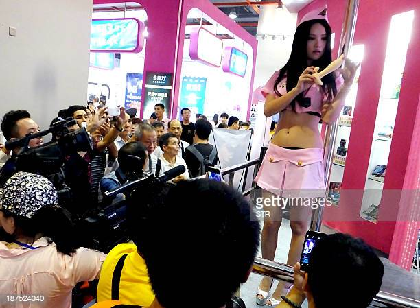 Visitors gather to watch a promoter showing off a sex toy at the Guangzhou Sex Culture Festival in Guangzhou south China's Guangdong province on...