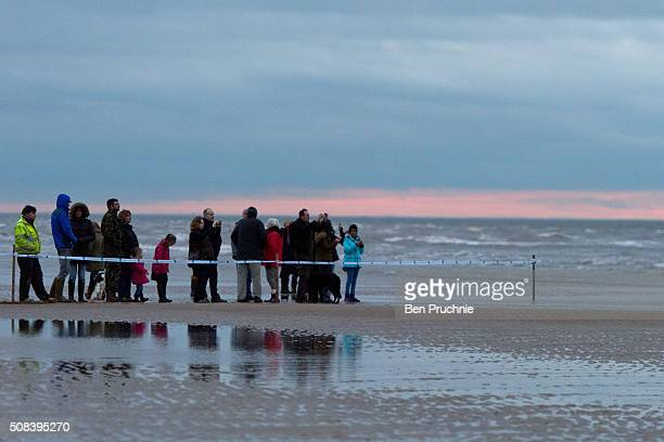 Visitors gather to watch a sperm whale that is stranded on a beach between Old Hunstanton and Holme on February 4 2016 in Hunstanton England The...