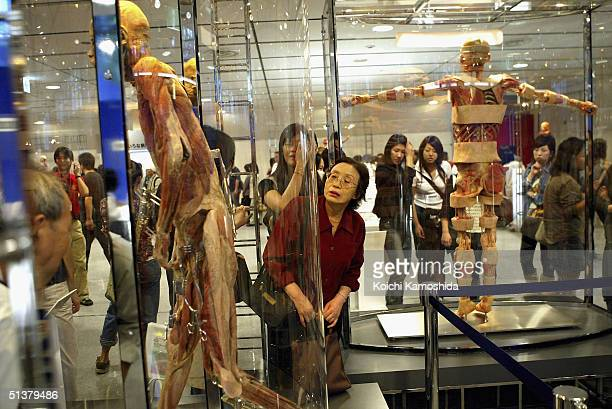 Visitors gaze at preserved whole body specimens at the Mysteries of the Human Body exhibition which displays some 170 specimens on October 1 2004 in...
