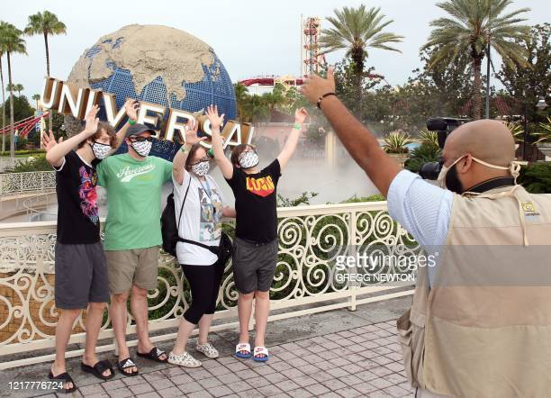 Visitors get a souvenir snapshot at Universal Studios theme park on the first day of reopening from the coronavirus pandemic, on June 5 in Orlando,...