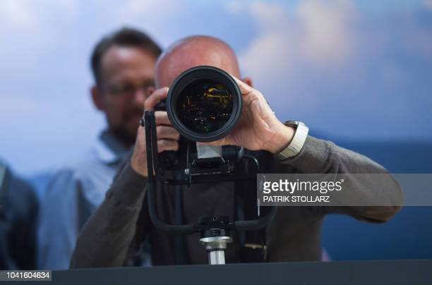 Visitors get to grip Canon cameras at the Canon stand at the Photokina trade fair in Cologne western Germany on September 27 2018 The fair for the...