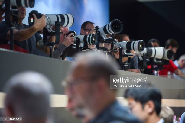 Visitors get to grip Canon cameras at the Canon stand at the Photokina trade fair in Cologne, western Germany on September 27, 2018. - The fair for...