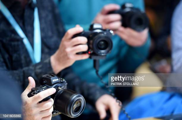 Visitors get to grip with a Nikon camera at the Nikon stand at the Photokina trade fair in Cologne, western Germany on September 27, 2018. - The fair...
