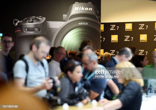 Visitors get to grip with the Nikon cameras at the Nikon stand at the Photokina trade fair in Cologne western Germany on September 27 2018 The fair...