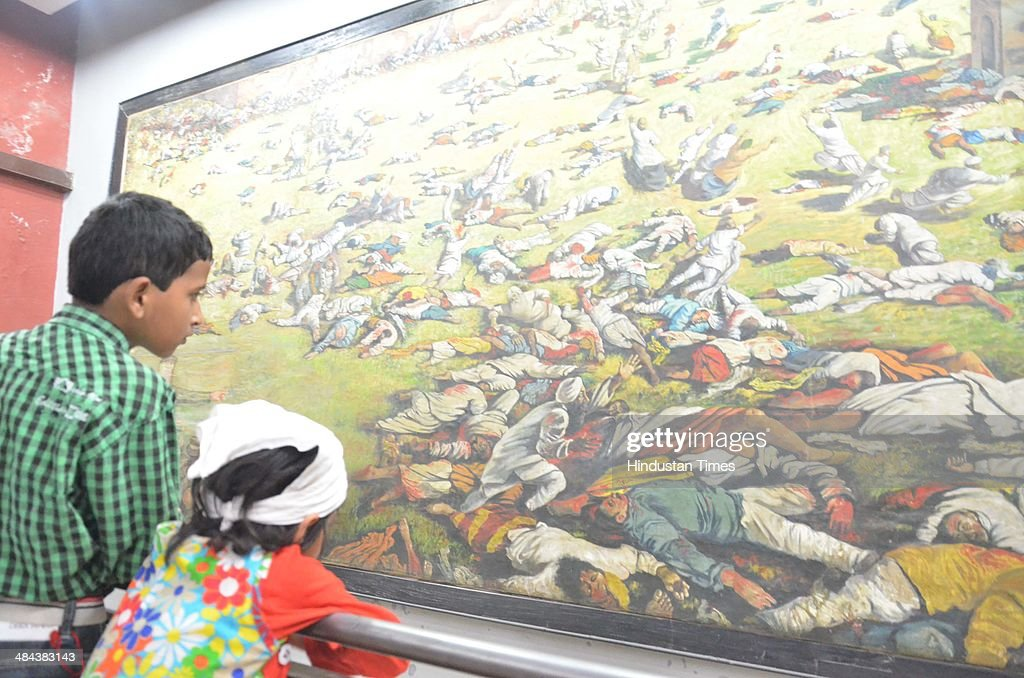 Visitors have a look at a picture of the martyrs on the eve of 95th anniversary of Jallianwala Bagh massacre at Jallianwala Bagh on April 12 2014 in..
