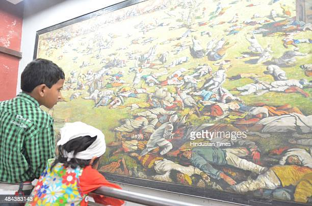 Visitors have a look at a picture of the martyrs on the eve of 95th anniversary of Jallianwala Bagh massacre at Jallianwala Bagh on April 12 2014 in...