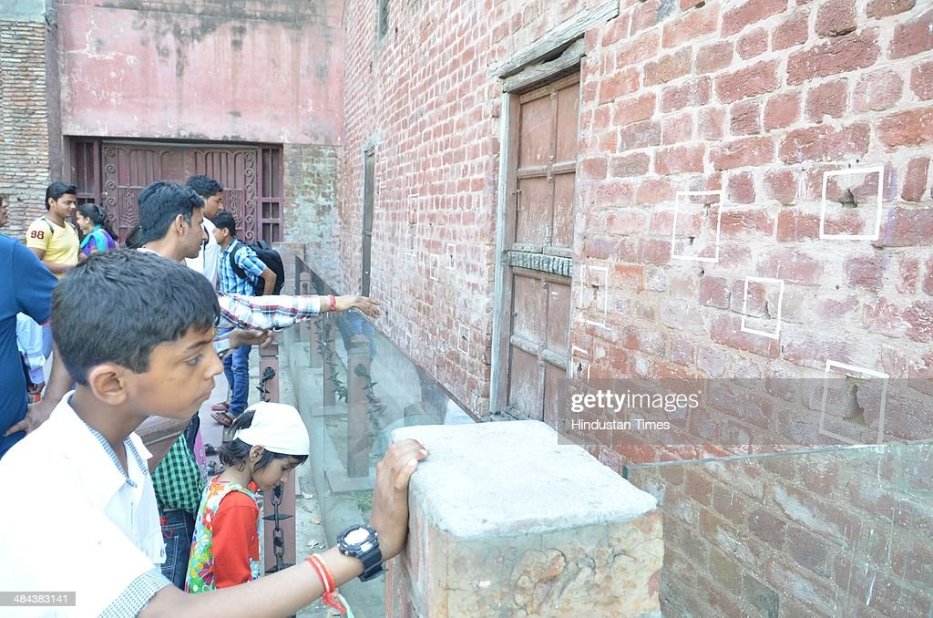 Visitors have a look at the bullet marks on a wall on the eve of 95th anniversary of Jallianwala Bagh massacre at Jallianwala Bagh on April 12 2014...