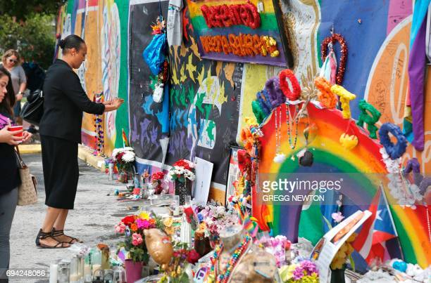 Visitors have a walk around the makeshift memorial outside the Pulse nightclub one year after the massacre in Orlando Florida on June 9 2017 In the...