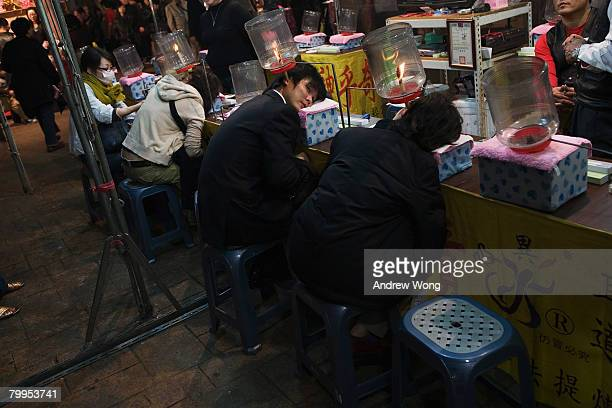 Visitors have their ears cleaned by a traditional way at a funfair on February 22, 2008 in Taipei. Taiwan was ceded by imperial China to Japan in...
