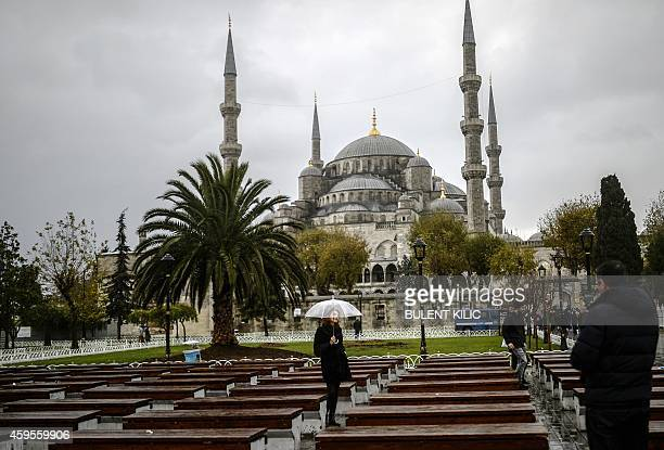 Visitors have their photograph taken in front of the Blue Mosque in Istanbul on November 25 2014 Pope Francis will visit Turkey on November 2830...