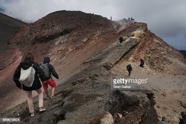 Visitors hike among craters and gravellike ash near the peak of Mount Etna on the island of Sicily on May 28 2017 near Catania Italy Mount Etna is...
