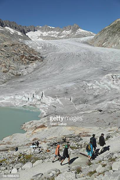 Visitors hike towards the bottom of the Rhone glacier at a small lake on August 22 2016 near Gletsch Switzerland In the last 120 years the Rhone...