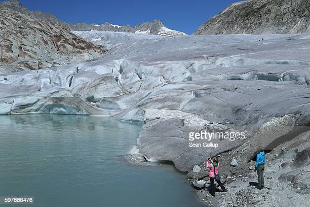 Visitors hike towards the bottom of the Rhone glacier at a small lake created by melting ice on August 22 2016 near Gletsch Switzerland In the last...