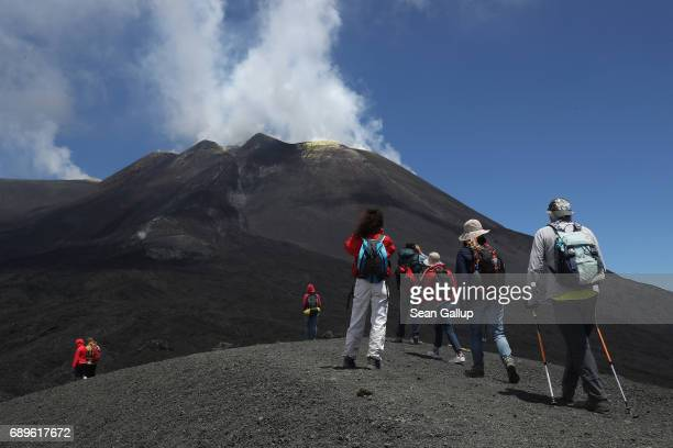 Visitors hiking among craters and gravellike ash gaze at the peak of Mount Etna on the island of Sicily on May 28 2017 near Catania Italy Mount Etna...
