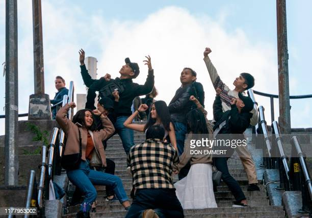 "Visitors hold a Joker pose for pictures on the staircase in the Bronx, made famous by the movie ""Joker,"" October 23, 2019 in New York. - In the Bronx..."