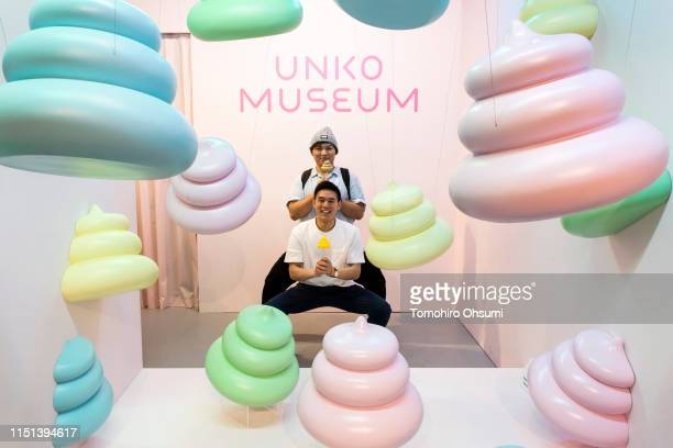Visitors hold poop figurines as they pose for a photograph at the Unko Museum Yokohama on May 24 2019 in Yokohama Japan The temporary popup museum...