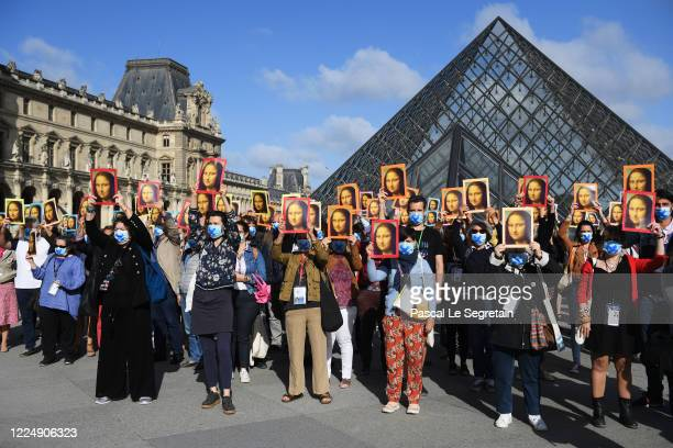 Visitors hold reproductions of the Mona Lisa outside the Louvre museum as it reopens its doors following its 16 week closure due to lockdown measures...