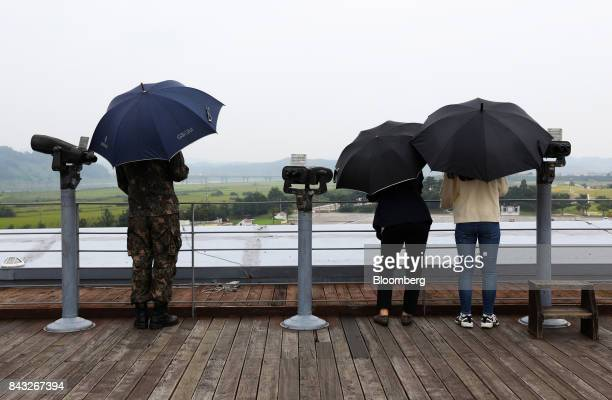 Visitors hold umbrellas as they look across to the north side of the border at the Imjingak pavilion near the Demilitarized Zone in Paju South Korea...
