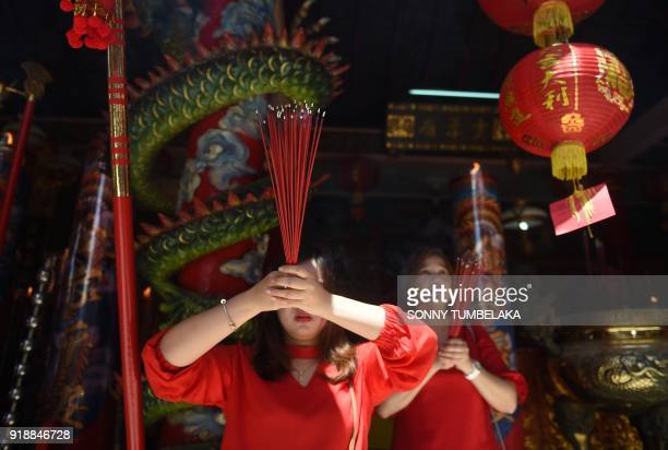 Visitors hold up incense sticks and pray at a Chinese temple to mark the start of the Lunar New Year in Kuta near Denpasar on Indonesia's Bali island...