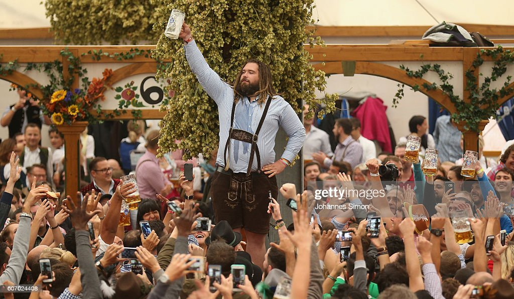 Visitors hold up one-liter glasses of beer to kick off the 2016 Oktoberfest beer & Opening Day - Oktoberfest 2016 Photos and Images | Getty Images