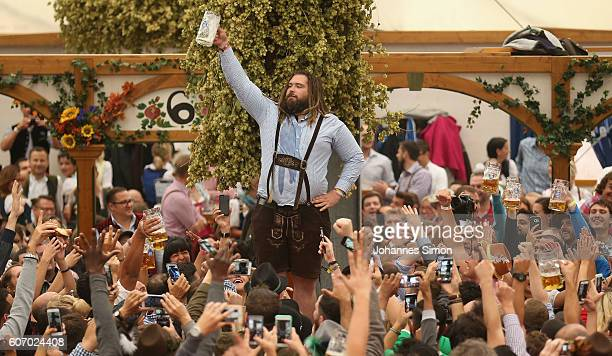 Visitors hold up oneliter glasses of beer to kick off the 2016 Oktoberfest beer festival in the Hofbraeu tent at Theresienwiese on September 17 2016...