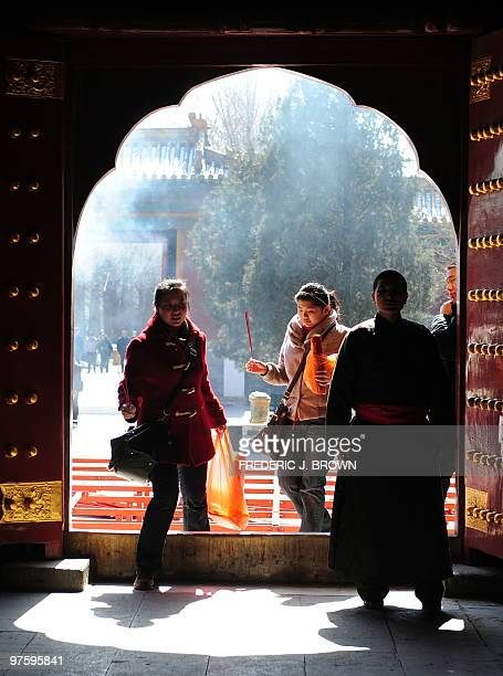Visitors holding sticks of burning incense walk behind a Tibetan Buddhist monk through a doorway at the Yonghegong also known as the Lama Temple a...