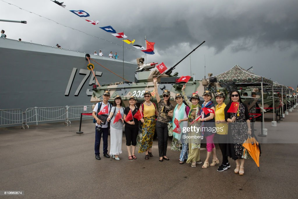 Visitors holding the flags of China and the Hong Kong Special Administrative Region pose for photographs in front of a People's Liberation Army (PLA) tank during an open day at the Ngong Suen Chau Barracks in Hong Kong, China, on Saturday, July 8, 2017. China's bid to display some soft power in Hong Kong-- with a visit by the country's first aircraft carrier -- has also showcased its heavy-handed approach to security. Photographer: Billy H.C. Kwok/Bloomberg via Getty Images