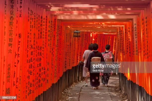 Visitors in a columned walkway at Fushimi Inari shrine, Kyoto, Japan