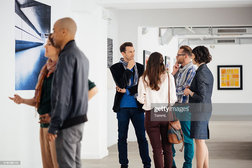 Visitors In Art Gallery Looking At Artwork And Talking : Stock Photo