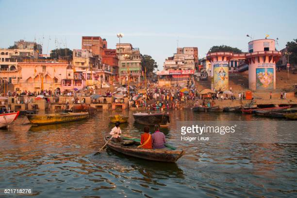 Visitors in boat on Ganges river in front of Dasaswamedh Ghat