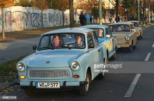 Visitors in East Germanera Trabant cars drive next to a stillstanding section of the Berlin Wall at Bornholmer Strasse where nearly 25 years before...