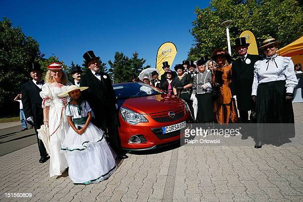 Visitors in historic costumes stand around an Opel Corsa at the manufacturing plant of German car maker Adam Opel GmbH on September 8 2012 in...