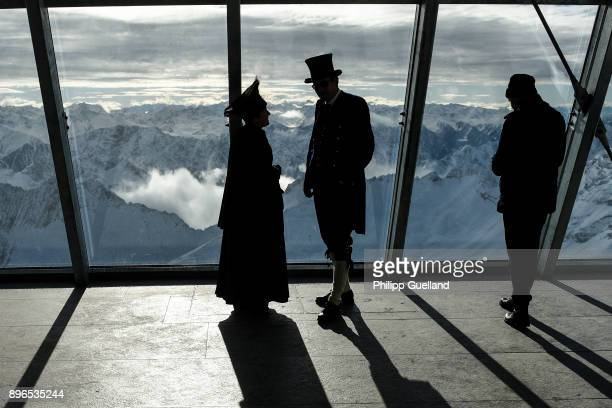 Visitors in historical clothing are silhouetted in front of snow covered mountains at the summit station of the new 'Eibsee Seilbahn' cable car...