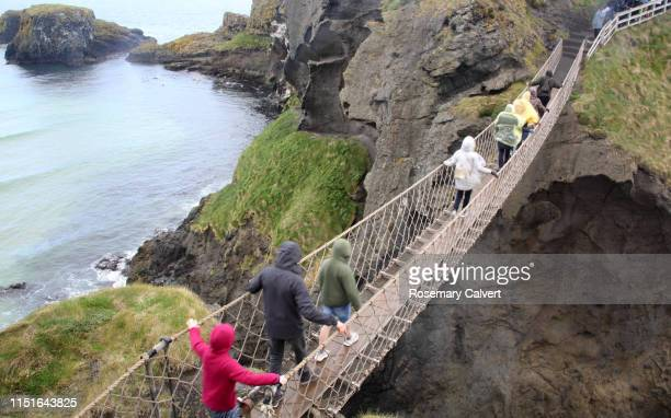 visitors in raincoats crossing carrick-a-rede rope bridge. - northern ireland stock pictures, royalty-free photos & images