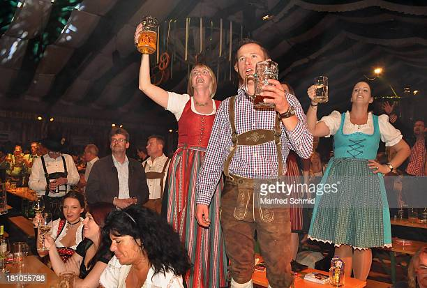 Visitors in traditional Austrian Lederhose and Dirndl pose during the Wiener Wiesn preopening party on September 18 2013 in Vienna Austria