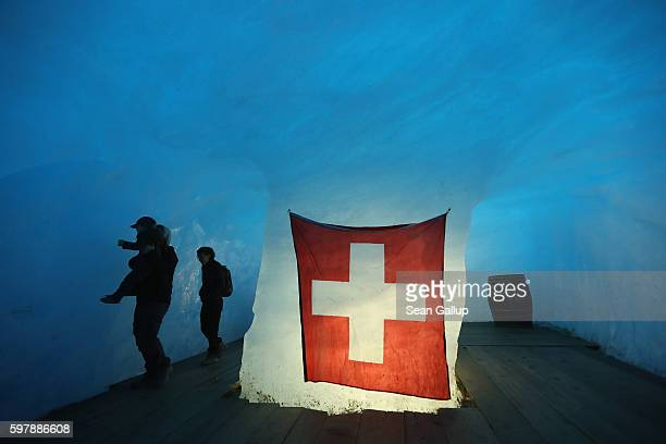 Visitors including a father holding his young son up to touch the ice wall stand inside a room with a Swiss flag that lies at the end of a...