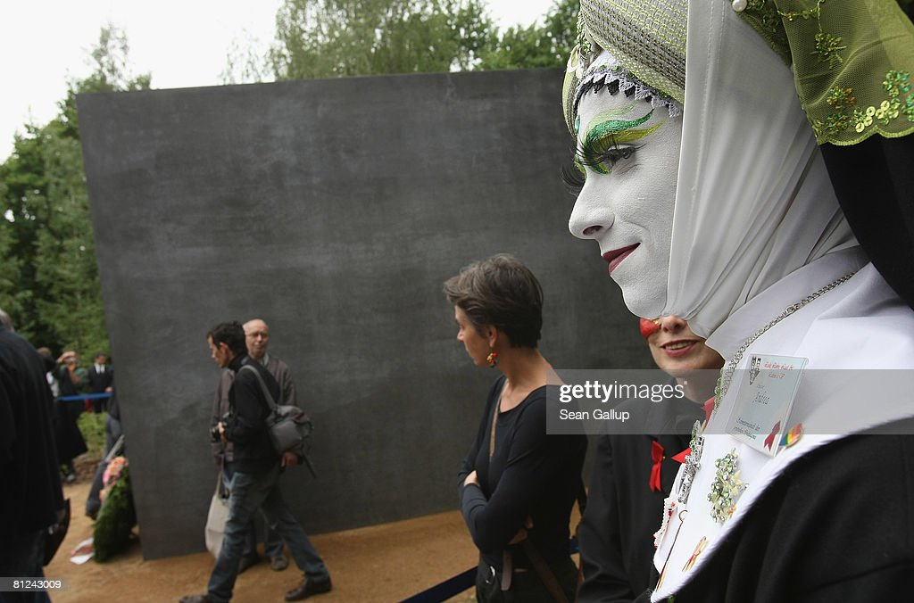Visitors, including a transvestite, line up to peek into the window of the just-inaugurated memorial to homosexual victims of the Nazis on May 27, 2008 in Berlin, Germany. The memorial, a large stone with a window that looks onto an image of two men kissing, commemorates the tens of thousands of gays imprisoned by the Nazis, including the estimated 15,000 sent to concentration camps. The memorial stands in the Tiergarten park close the to Holocaust Memorial.