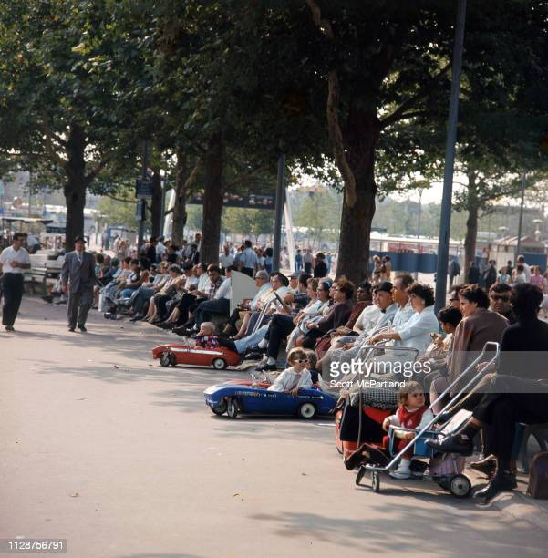 Visitors including children in strollers take a break and relax on park benches in Flushing Meadows Park during the World's Fair in Queens New York...