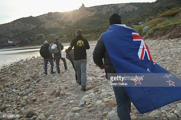 Visitors including one wearing a New Zealand flag who had attended the Dawn Service at the Anzac Commemorative Site walk along the beach at Anzac...