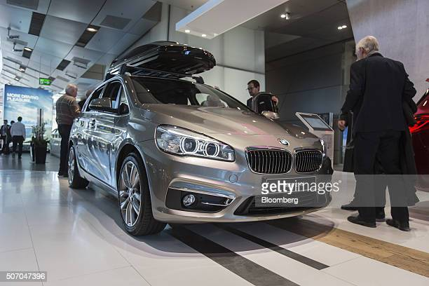Visitors inspect a BMW 214d automobile produced by Bayerische Motoren Werke AG inside the BMW World showroom in Munich Germany on Tuesday Jan 26 2016...