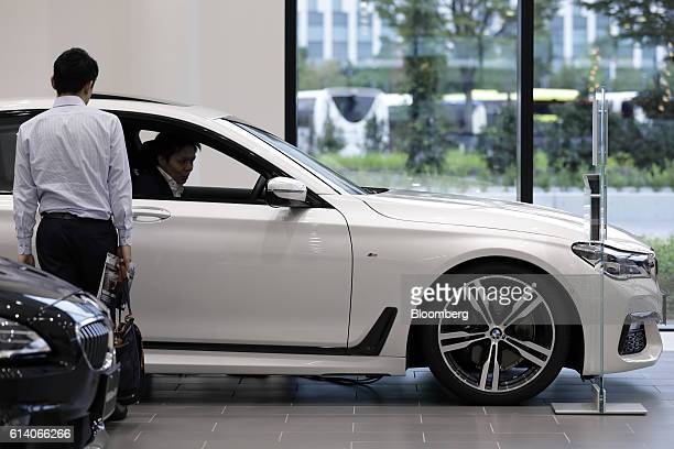 Visitors inspect a BMW 740i M Sport sedan manufactured by Bayerische Motoren Werke AG on display at the BMW Group Tokyo Bay showroom in Tokyo Japan...