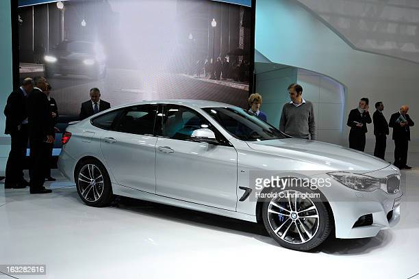 Visitors inspect a BMW Series 3 Gran Turismo during the 83rd Geneva Motor Show on March 6 2013 in Geneva Switzerland Held annually with more than 130...